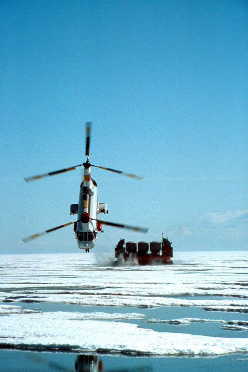 Photo of a helicopter towing a 'hover-barge' in the Arctic