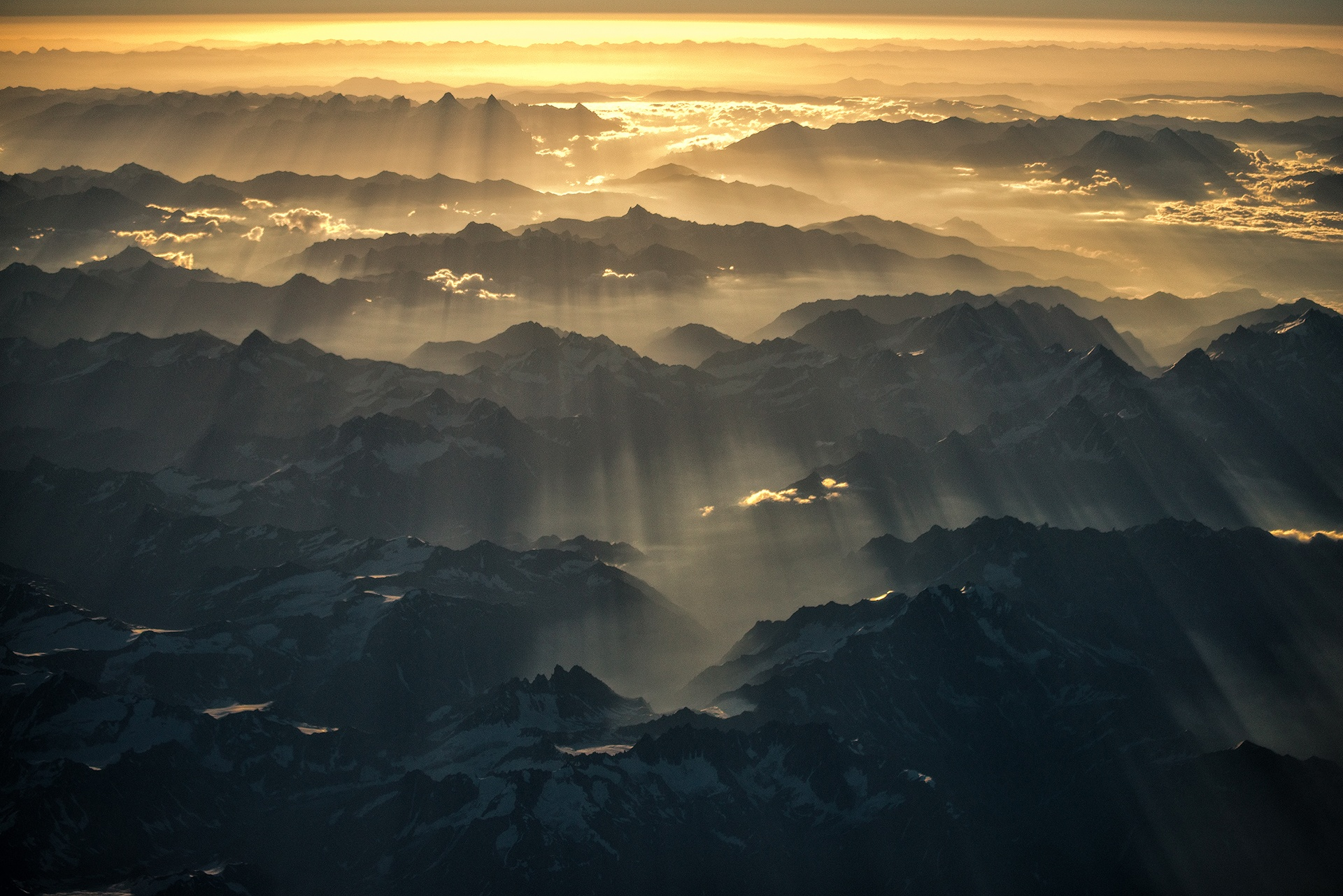 Streaks of sunlight shine over the Himalayas at dawn by Nutthavood Punpeng